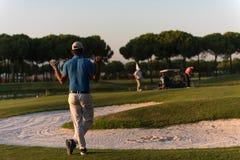 从后面的高尔夫球运动员在看对在距离的孔的路线 免版税库存图片