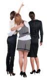 后面看法三个年轻人女商人指向。 免版税库存图片