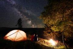 后面看法人和女孩在露营地附近坐并且看灼烧的火在晚上在满天星斗的天空下 库存照片