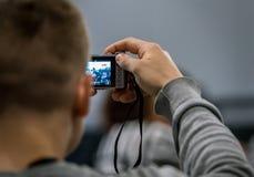 后面看法关闭拍与一部袖珍相机的一个人照片 免版税图库摄影