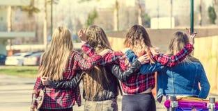 后面看法四个女朋友拥抱 免版税库存照片