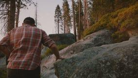 后面看法年轻自由人远足,上升在大岩石在美丽的日落优胜美地国立公园森林慢动作 影视素材