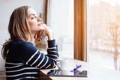 后面看法微笑的美丽的少妇在大窗口附近读了与数字式片剂的杂志在咖啡馆或家 有吸引力的 库存照片