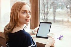 后面看法微笑的美丽的少妇在大窗口附近读了与数字式片剂的杂志在咖啡馆或家 有吸引力的 免版税库存照片