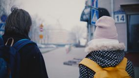 后面看法愉快的轻松的年轻人和妇女握手的便衣发怒城市街道的在一个多雪的冷的冬日 影视素材