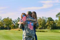 后面看法战士拥抱他的与美国旗子的家庭 免版税图库摄影