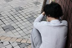 后面看法沮丧的被注重的年轻亚裔雇员人感人的头和感觉失望或用尽 失业的事务 库存照片