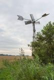 从后面看的全自动机械的金属风watermill 免版税库存图片