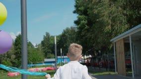 后面神色年轻男孩跑绿色公园和举行五颜六色的气球 影视素材