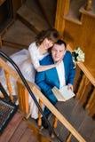 后面美丽的肉欲的新娘拥抱从她拿着书的英俊的新郎在老图书馆木台阶  免版税图库摄影