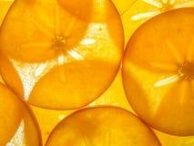 后面背景点燃了被安排的成熟亚洲柿树persimon切片 免版税库存照片