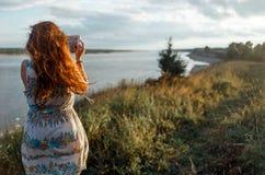 后面观点的一个少妇流浪汉做与便携式的片剂照相机的照片在她的假期期间在村庄草甸 免版税库存图片
