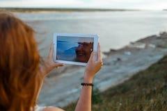 后面观点的一个少妇流浪汉做与便携式的片剂照相机的照片在她的假期期间在村庄草甸 库存照片