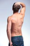 后面观点的一个露胸部的年轻人 库存图片