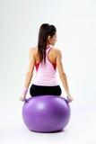 后面观点的一名年轻体育妇女坐与dumbells的fitball 库存图片