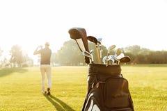 后面观点的一家男性高尔夫球运动员摇摆的高尔夫俱乐部 免版税库存照片