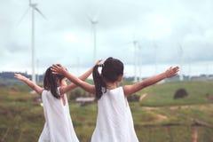 后面观点的两个亚裔儿童女孩举他们的胳膊 库存图片