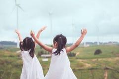 后面观点的两个亚裔儿童女孩举他们的胳膊 库存照片