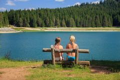 后面观点的两个女孩坐长凳在山湖和杉树附近 免版税库存照片