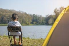 后面观点的亚裔儿童男孩坐放松的一把椅子在野营在有迷离水源和森林背景的帐篷 免版税库存照片