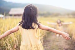 后面观点的亚裔小孩女孩举她的手 库存照片