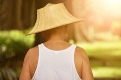 后面观点的亚裔男性花匠 他戴太阳的一个帽子保护 库存图片