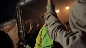 后面观点的人人群音乐会的 英尺长度 音乐会剪影在明亮的阶段光前面拥挤 股票视频