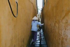 后面观点的传统帽子运载的自行车的越南妇女在狭窄的街道上在会安市,越南 图库摄影