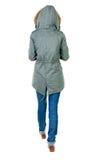 后面观点的冬天夹克的走的妇女有敞篷的 免版税库存图片