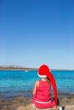 后面观点的圣诞老人帽子的可爱的小女孩 免版税库存图片