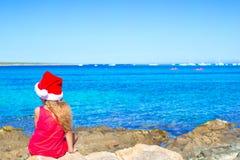 后面观点的圣诞老人帽子的可爱的小女孩 免版税图库摄影