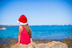 后面观点的圣诞老人帽子的逗人喜爱的小女孩在 免版税库存照片