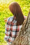 后面观点的在拿着笔记本的树旁边的女孩 库存照片