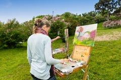 后面观点的在艺术课期间的一位被集中的女性画家 免版税库存图片
