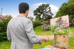 后面观点的在艺术课期间的一位被集中的男性艺术家 库存照片