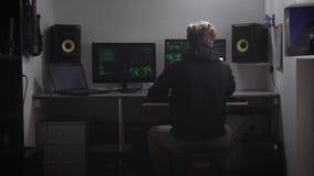 后面观点的坐在桌上的黑衣裳的一个人 网络间谍乱砍从他的室的计算机数据库  股票视频