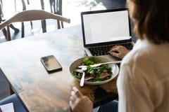 后面观点的女实业家有lucnch在咖啡馆 免版税库存照片