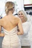 后面观点的妇女在有愉快资深所有者协助的新娘婚装穿戴了 库存图片
