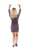 后面观点的妇女推挤墙壁 查出在空白背景 免版税图库摄影