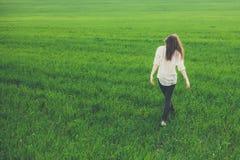 后面观点的孤独的女孩在草甸 免版税库存图片