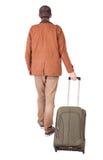 后面观点的带着手提箱的走的人 免版税库存照片