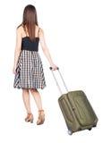 后面观点的带着绿色手提箱的走的妇女 免版税库存图片