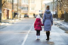 后面观点的年轻亭亭玉立的可爱的妇女母亲和小儿童走女孩的女儿温暖的衣物的一起握手  免版税库存照片
