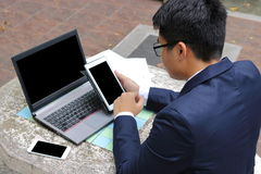 后面观点的年轻英俊的商人使用片剂,并且他的工作的膝上型计算机在户外公众的大理石停放 库存图片