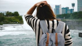 后面观点的愉快的年轻旅游妇女用在尼亚加拉大瀑布瀑布慢动作的背包观看的冲的水 股票视频