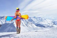 后面观点的拿着在头上的比基尼泳装的女孩雪板 免版税库存图片