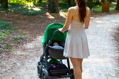 后面观点的拿着有里面她愉快的逗人喜爱的婴孩的美丽的夏天礼服的妇女摇篮车,有婴儿走的母亲 免版税库存照片