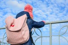 后面观点的有一个背包的儿童女孩,在一件被编织的帽子和夹克,与云彩的背景蓝天 库存照片