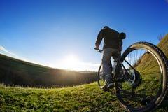 后面观点的有一辆自行车的一个人反对蓝天 骑自行车者骑自行车 图库摄影