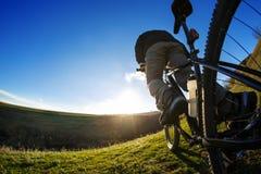 后面观点的有一辆自行车的一个人反对蓝天 骑自行车者骑自行车 库存图片